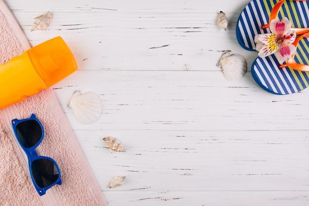 Concepto de vacaciones de vacaciones de verano. protector solar, zapatillas y gafas de sol sobre una toalla alrededor de las conchas. vista superior y endecha plana.