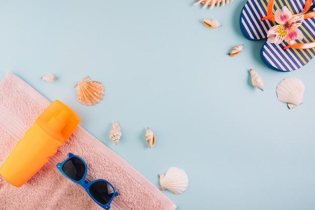 Concepto de vacaciones de vacaciones de verano. protector solar, zapatillas y gafas de sol sobre una toalla alrededor de las conchas.