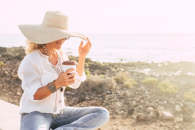 Concepto de vacaciones, vacaciones, viajes y personas de verano - mujer sonriente con sombrero para el sol en la playa sobre el mar y el cielo blanco. taza de café y mujer feliz
