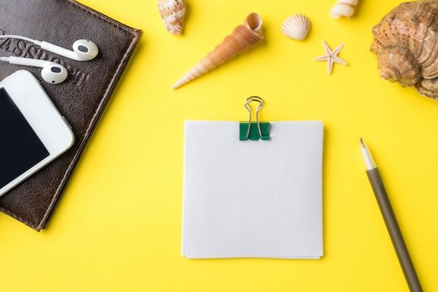 El concepto de vacaciones de verano. bloc de notas del teléfono pasaporte. lugar para texto conchas marinas sobre fondo amarillo
