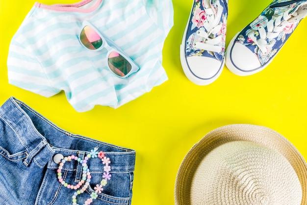 Concepto de vacaciones de verano, conjunto de ropa de verano para niños: pantalones cortos para niños, camiseta, sombrero, gafas de sol, collar de pulsera, zapatillas de deporte, mesa plana de color amarillo brillante.