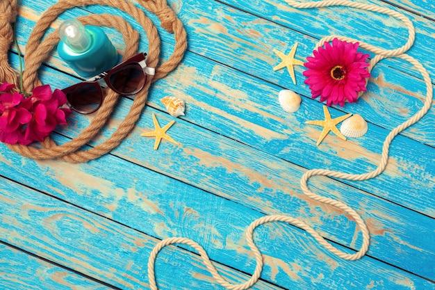 Concepto de vacaciones de verano de cuerdas, gafas de sol y flores de color rosa sobre fondo de madera azul