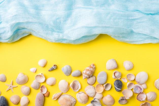 El concepto de vacaciones de verano. fondo amarillo de conchas marinas bufanda azul imitación mar