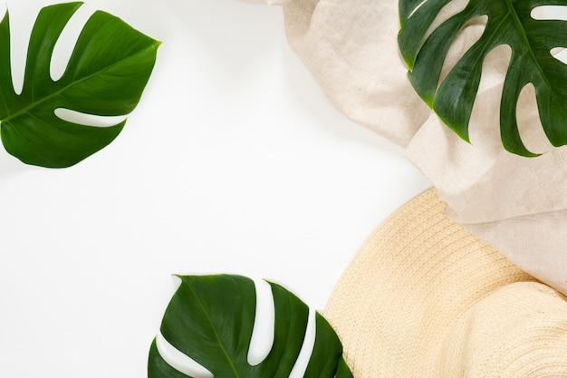 Concepto de vacaciones de verano con hojas de monstera tropical y sombrero de paja sobre fondo blanco.