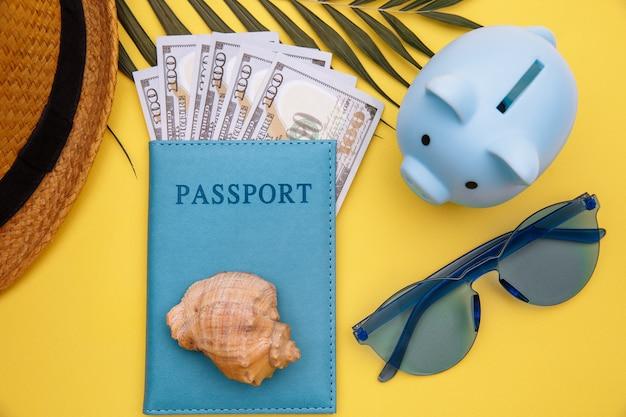 Concepto de vacaciones de verano. pasaporte con dinero, gafas de sol y hucha azul en primer plano de la mesa amarilla.