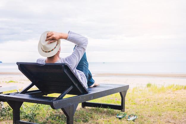 Concepto de vacaciones de verano. playa. los hombres asiáticos usan sombreros, se relajan y sostienen un sombrero para dormir en una silla de playa en prachuap khiri khan.