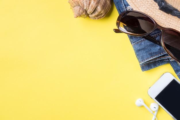 El concepto de vacaciones de verano. sombrero gafas de sol conchas marinas sobre fondo amarillo