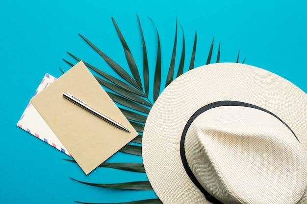 Concepto de vacaciones de verano. sombrero de hombre, sobre, bolígrafo y rama de palma sobre un fondo brillante
