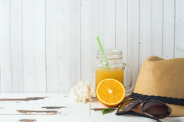 Concepto de vacaciones de verano. sombrero de paja con zumo de naranja y conchas. copia espacio
