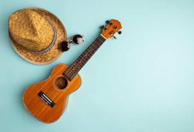 Concepto de vacaciones de verano con ukelele y sombrero de paja sobre fondo turquesa pastel abstracto con espacio de copia. laicos planos creativos.
