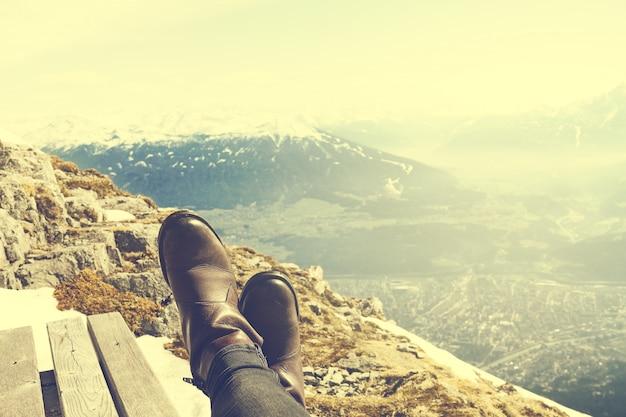 Concepto de las vacaciones del viaje. pies de las piernas de chica joven escalofriante en banco de madera sobre fondo de montaña de la naturaleza. horizontal. viraje.