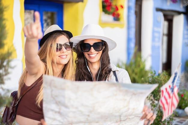 Concepto de vacaciones, viajes, amigos y turismo. americanas chicas guapas mirando mapa turístico de la ciudad