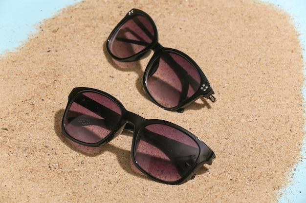 Concepto de vacaciones de viajes de playa de verano. gafas de sol en la arena en un día soleado.