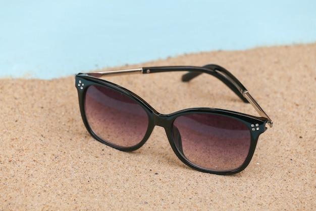 Concepto de vacaciones de viajes de playa de verano. gafas de sol sobre arena.