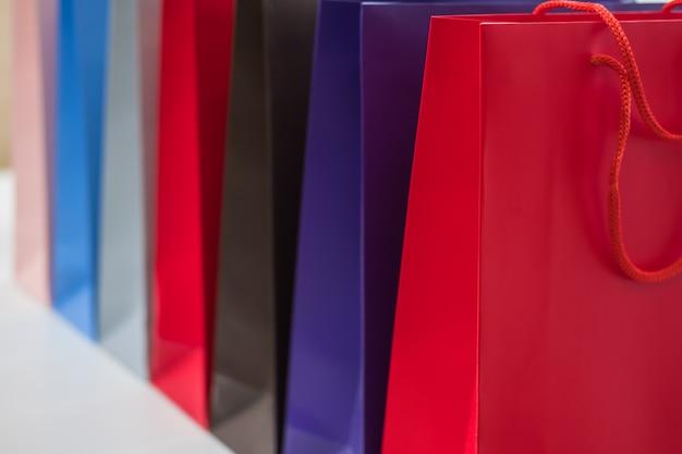 Concepto de venta, consumo, publicidad y venta por menor - muchos bolsos de compras coloridos