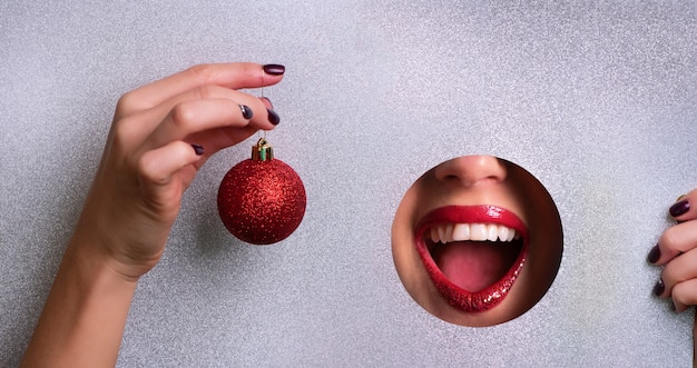 Concepto de venta de invierno. labios rojos en el agujero de papel plateado con efecto metálico, mano que sostiene la bola roja brillante de navidad.