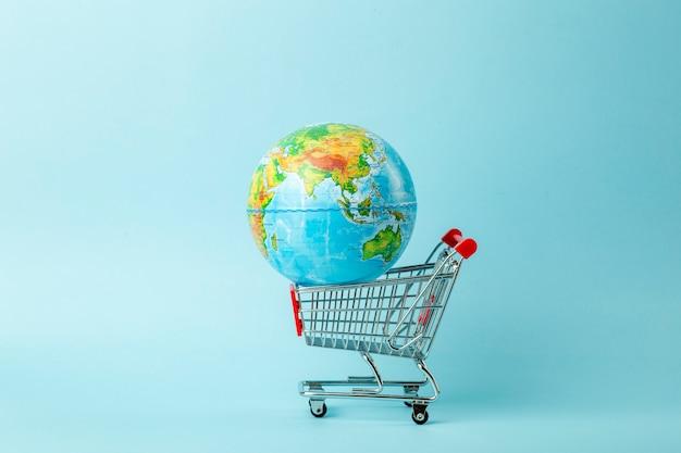Concepto de venta mundial y venta por internet. carro de supermercado con globo de tierra sobre fondo azul. comercio mundial y entrega de compras