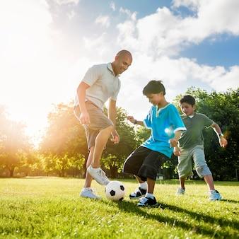Concepto de verano de la actividad del padre hijo del fútbol campo