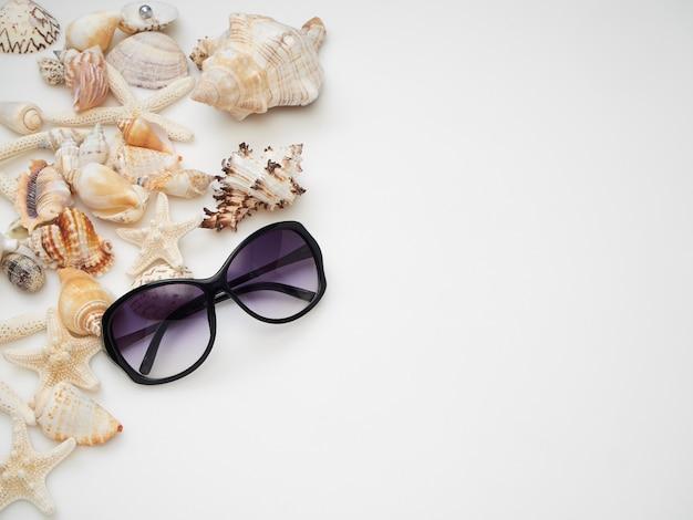 Concepto de verano conchas, estrellas de mar, gafas de sol sobre un fondo blanco.
