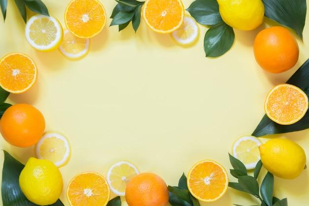 Concepto de verano conjunto de frutas tropicales, limón, naranja y hojas verdes sobre amarillo.