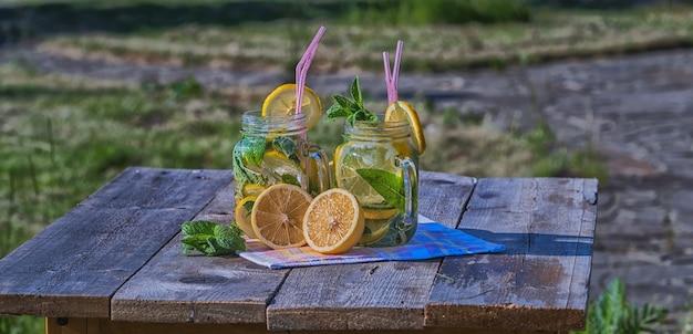 Concepto de verano. limonada casera con limón, menta y hielo en vasos, sobre mesa de madera, al aire libre.