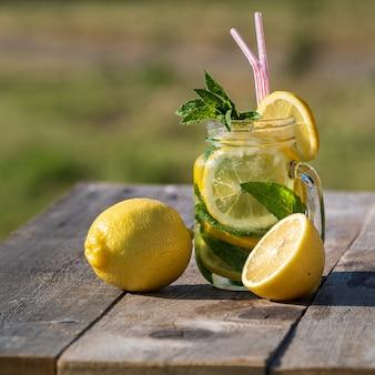 Concepto de verano limonada con el limón, la menta y el hielo en un tarro, sobre la tabla de madera vieja, al aire libre.