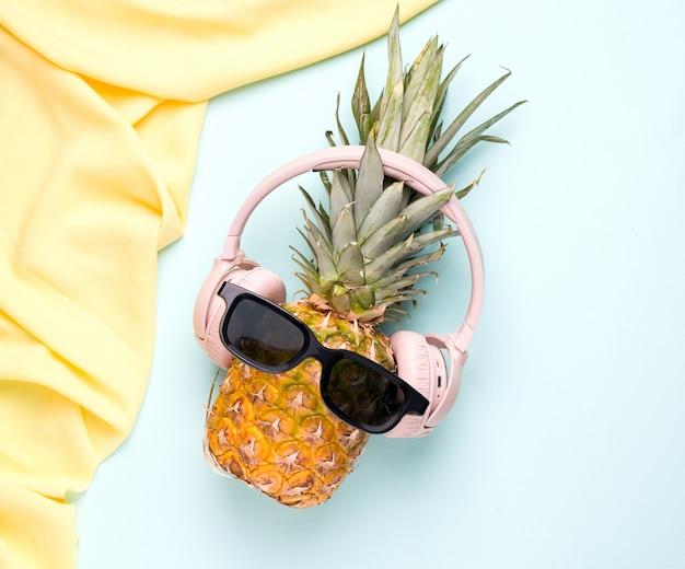 Concepto de verano con piña tropical en gafas de sol y auriculares en un espacio azul.