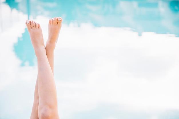 Concepto de verano y piscina con piernas