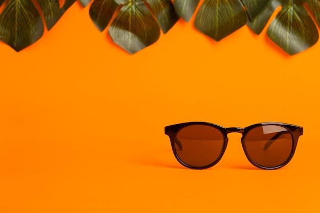 Concepto de verano y vacaciones. gafas de sol y hojas tropicales sobre un fondo de color naranja