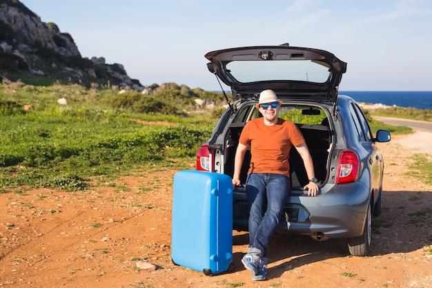 Concepto de verano, vacaciones, viajes y vacaciones - hombre cerca del coche listo para viajar.