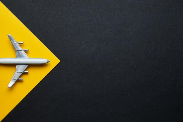 Concepto de viaje aéreo de juguete sobre fondo amarillo y negro con espacio de copia