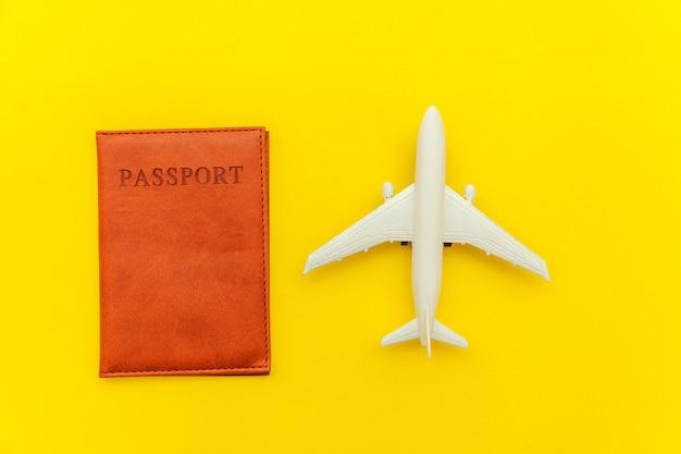 Concepto de viaje de aventura de viaje plano simple mínimo con avión y pasaporte sobre fondo moderno moderno amarillo
