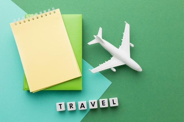 Concepto de viaje con avión blanco y cuadernos.