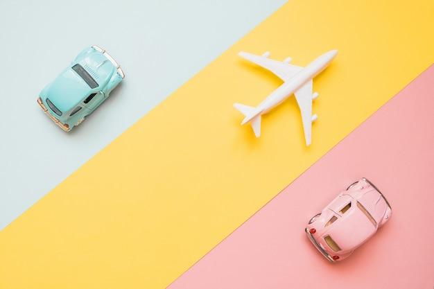 Concepto de viaje con avión y coches en azul, amarillo y rosa.