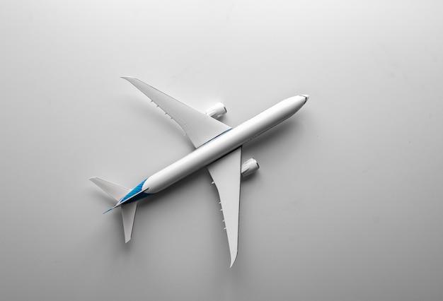 Concepto de viaje con avión de juguete sobre blanco. vista superior plana con espacio de copia