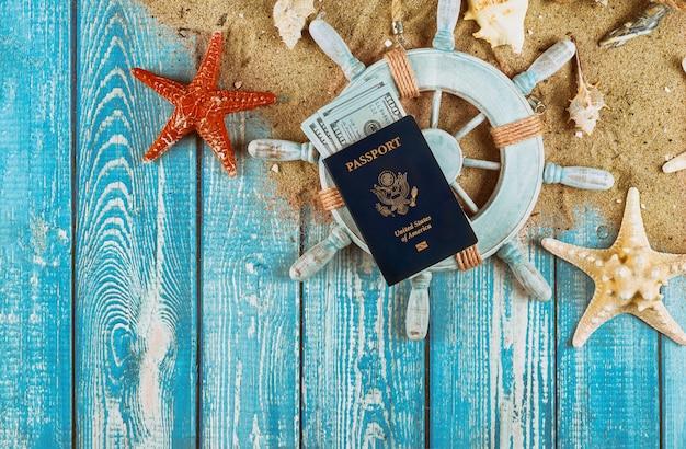Concepto de viaje del capitán steering con billetes de dinero en dólares en la estrella de arena de pescado y conchas pasaporte estadounidense sobre fondo de madera azul