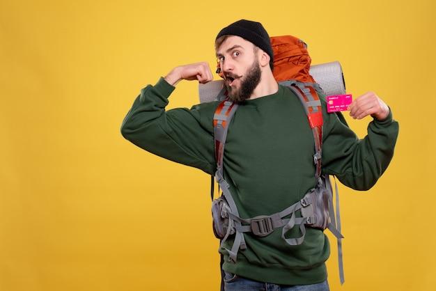 Concepto de viaje con chico joven ambicioso con packpack y sosteniendo una tarjeta bancaria mostrando musculoso en amarillo