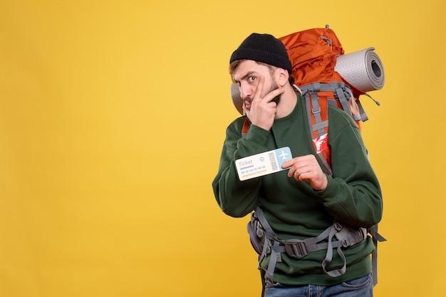 Concepto de viaje con chico joven curioso con packpack y billete mostrando en amarillo