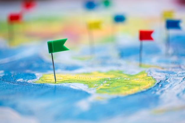 Concepto de viaje con chinchetas de bandera y mapa del mundo.