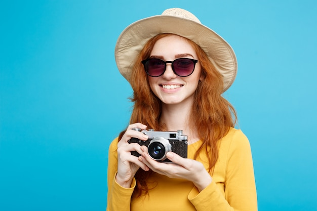 Concepto de viaje - close up retrato joven y bella chica atractiva redhair con sombrero de moda, gafas de sol y cámara vintage sonriendo a la cámara. pared azul pastel. copia espacio