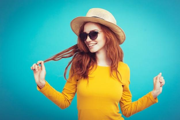 Concepto de viaje - close up retrato joven hermosa atractiva chica pelirroja con sombrero de moda y gafas de sol sonriendo. fondo de pastel azul. copie el espacio.