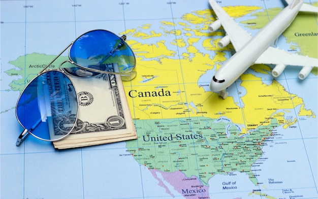 Concepto de viaje con dinero, avión y gafas de sol