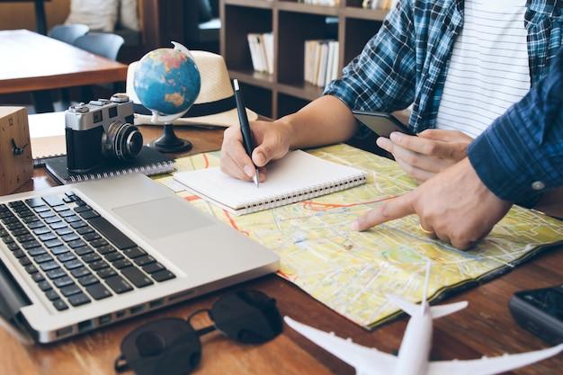 Concepto de viaje dos hombres que eligen el lugar de vacaciones, exploran el compromiso en el mapa, toman notas en el cuaderno