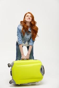 Concepto de viaje y estilo de vida: mujer joven sufre de dolor de espalda levantar una maleta pesada