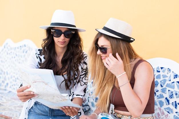 Concepto de viaje y estilo de vida tiempo de vacaciones, mujeres jóvenes viajeros sentados, tomando fotos y mirando en un mapa