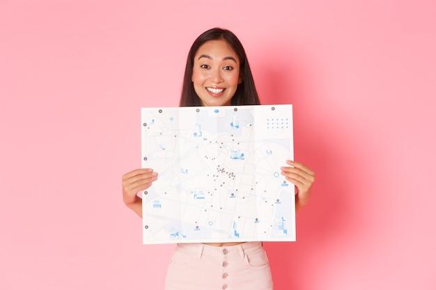 Concepto de viaje, estilo de vida y turismo. alegre y atractiva turista asiática explora la nueva ciudad, visita museos, muestra un mapa de la ciudad con visitas turísticas y una pared rosada y alegre