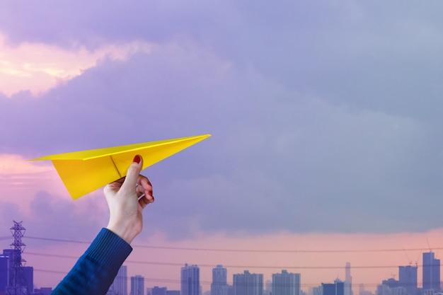 Concepto de viaje hipster woman o wanderlust girl levanta un avión de papel