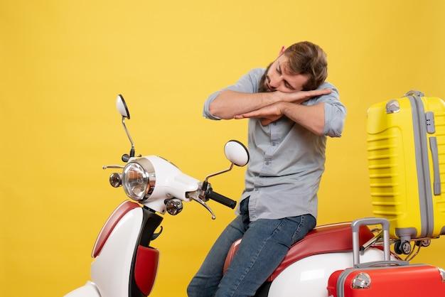 Concepto de viaje con hombre barbudo soñoliento joven sentado en moto en amarillo