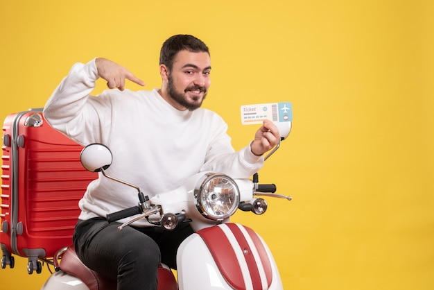 Concepto de viaje con hombre sonriente feliz sentado en motocicleta con maleta mostrando billete en amarillo Foto gratis