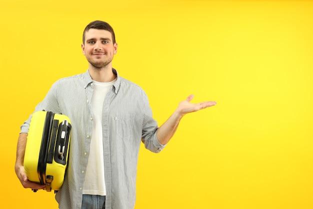 Concepto de viaje con joven sobre fondo amarillo, espacio para texto.